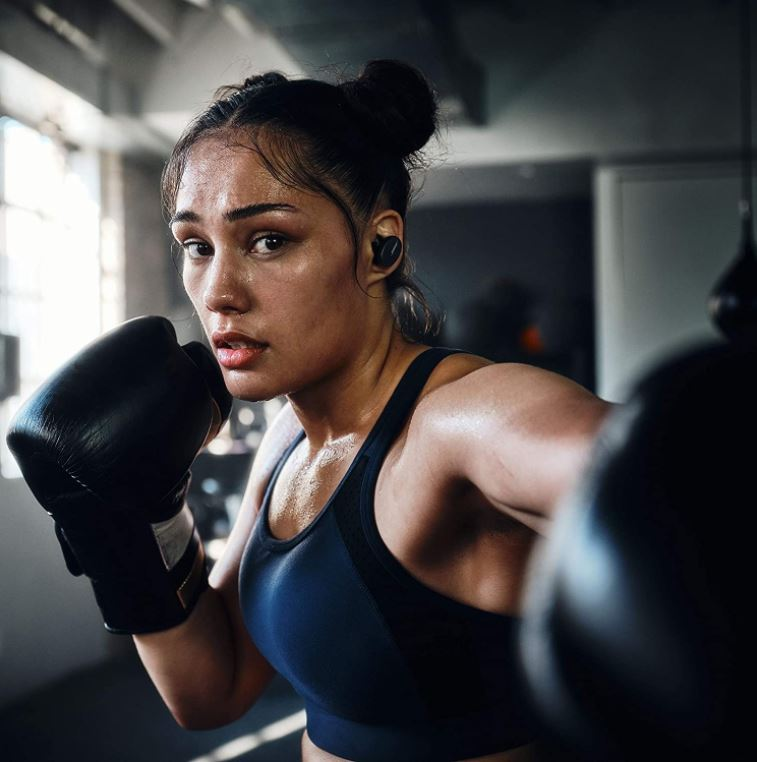 woman wearing earbuds while boxing